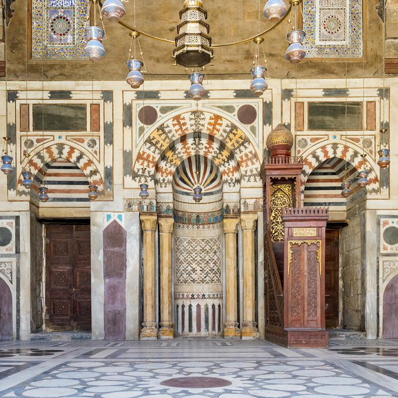 Colorful decorated marble wall with Mihrab and wooden minbar at mosque of Sultan Barquq, Cairo, Egypt. Colorful decorated marble wall with Mihrab - niche - and stock photography