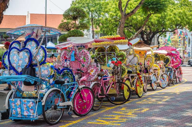 The colorful decorated rickshaws are parking in Dutch Square Malacca waiting for customers. royalty free stock image