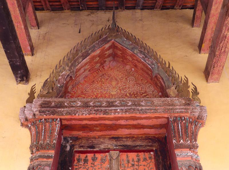 Colorful decoration of painting and carving on entrance door of a Buddhist temple`s chapel royalty free stock photography