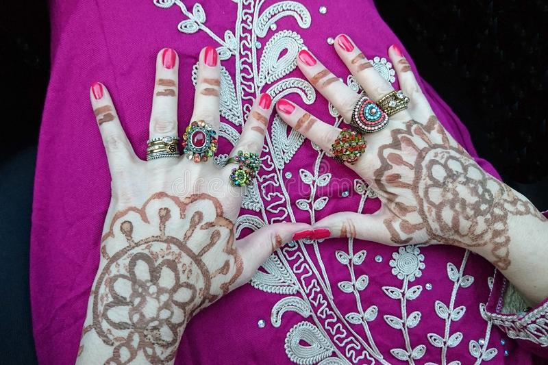 Wedding preparations: With henna and rings decorated hands on the lap of a woman in a Moroccan dress stock photography