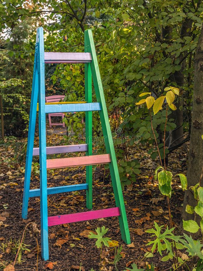 Colorful wooden ladder in the garden royalty free stock photo