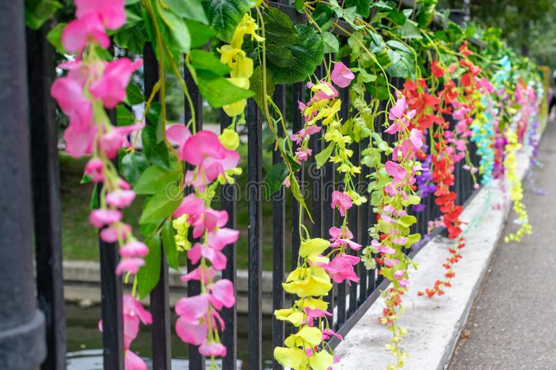 Colorful delicate beautiful fake artifical flowers decoration on a holiday street open air festival stock photo