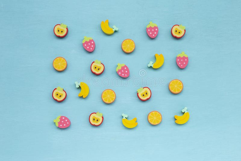 Colorful design fruit shape rubber on blue texture background stock photography