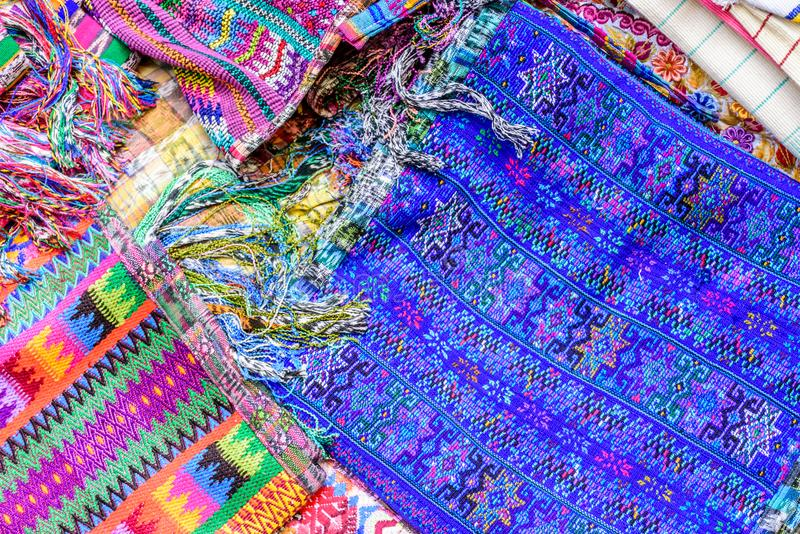Colorful display of handwoven Guatemalan textiles on market stall. Typical colorful handwoven Guatemalan textiles made & sold by local indigenous women at royalty free stock image