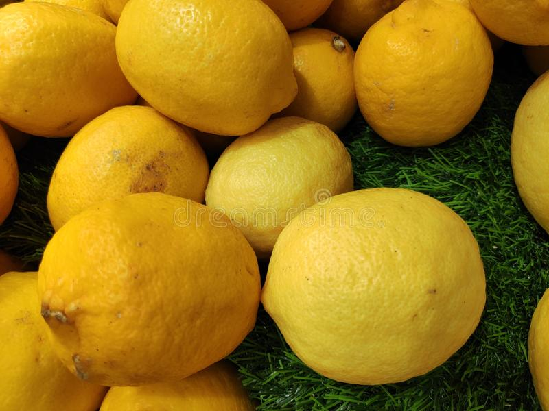 Colorful Display Of Lemons In Market. Ripe yellow lemons, stock photo