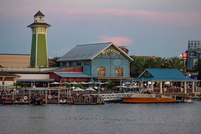 Colorful dockside and lighthouse on sunset background at Lake Buena Vista. Orlando, Florida. June 15, 2019. Colorful dockside and lighthouse on sunset royalty free stock images