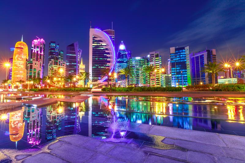 Colorful Doha West Bay. Capital of Qatar. Colorful Doha West Bay high rises illuminated at night reflections in downtown park. Scenic towers of Doha skyline stock photos