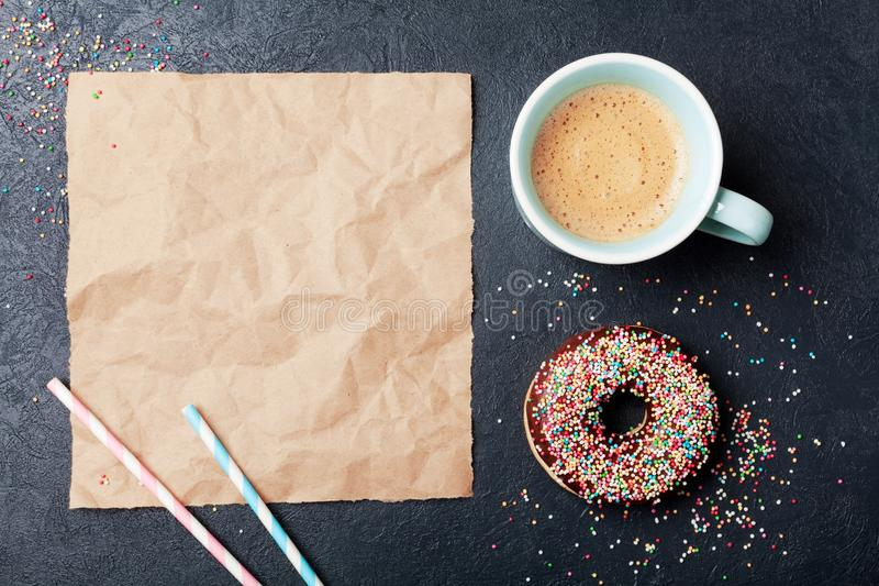 Colorful donut with cup of coffee on black table top view. Flat lay. Paper sheet for text. royalty free stock photos