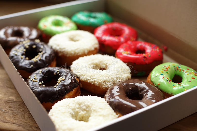 Colorful donuts in box. Full box, coconut topping stock photos
