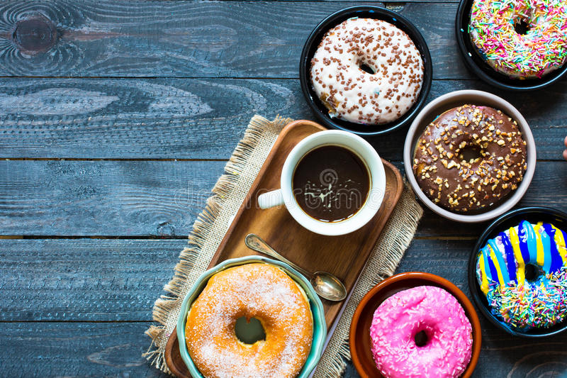 Colorful Donuts breakfast composition with different color styles. Of doughnuts and fresh coffee on the side over an aged wooden desk background royalty free stock photo