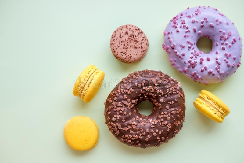 Colorful donuts and macaroons on wooden table. Top view with copy space. Unhealthy but tasty dessert royalty free stock image