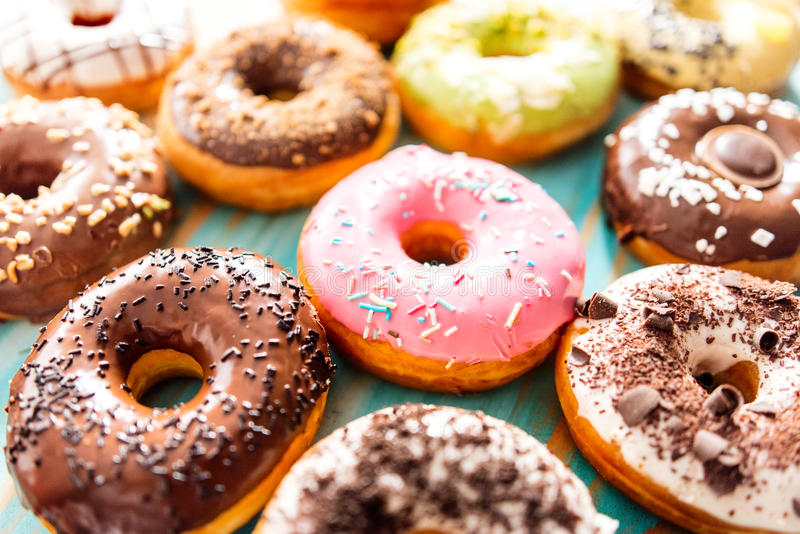 Colorful donuts. A variety of colorful donuts with different glazing and decorations. Chocolate, vanilla, caramel glazing and sprinkles, nuts and chocolate stock photo