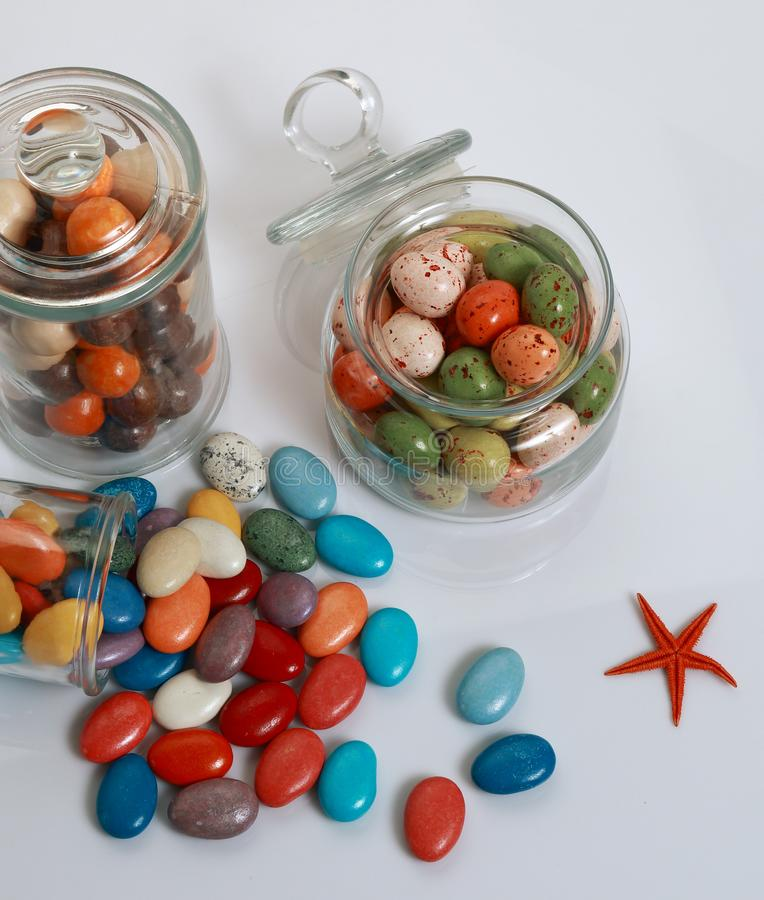 Colorful dragee candies in jars. Colorfully dragee candies in different shapes poured from transparent jars stock photo