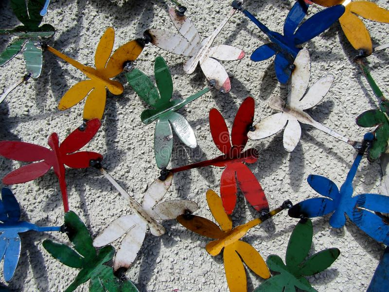 Colorful dragonflies made out of paint cans stock images