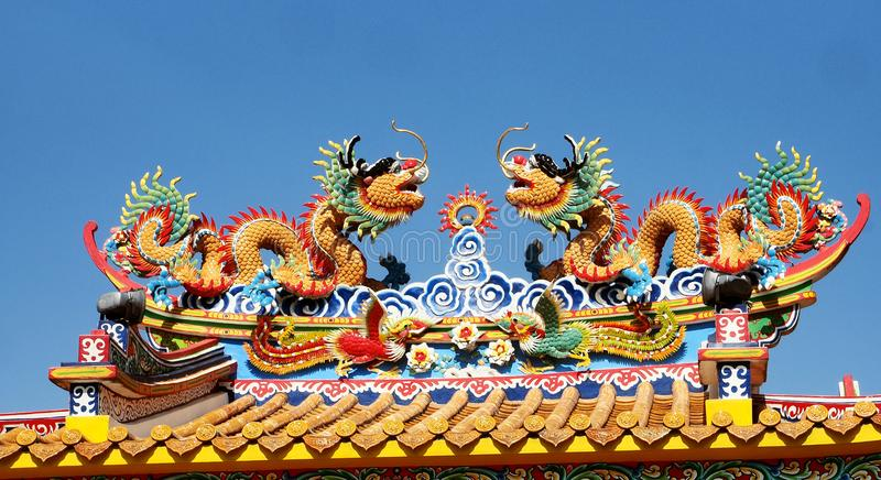 Colorful dragons at a Chinese shrine. Colorful dragons soar into blue sky at a Chinese shrine in Thailand royalty free stock photo
