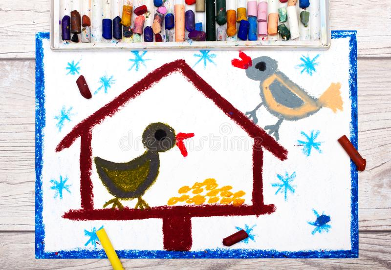 Colorful drawing: Bird feeder, winter and two cute birds. Feeder for the birds. Photo of colorful drawing: Bird feeder, winter and two cute birds. Feeder for the royalty free illustration