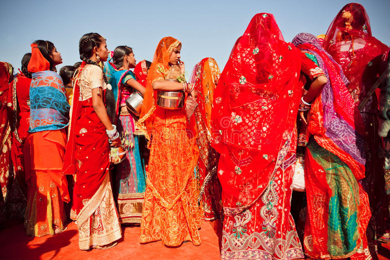 Colorful dressed young women in crowd of indian ladies stock images