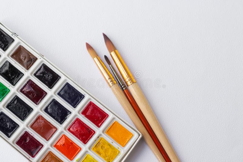 Colorful dry watercolor tablet set and white plastic palette and paint brushes and pencils on white texture background royalty free stock photography