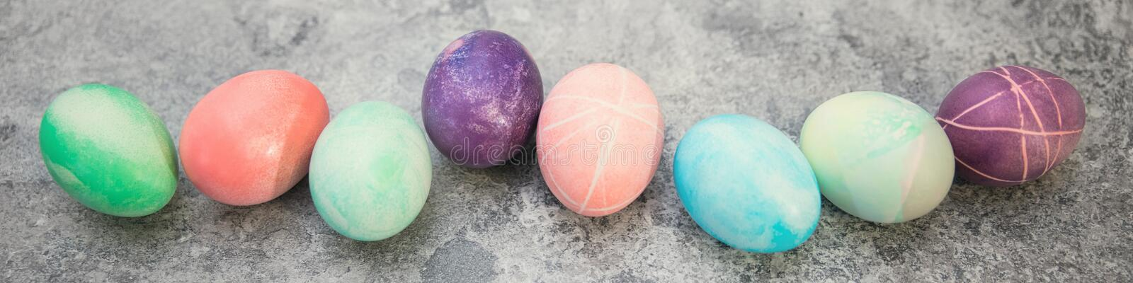 Colorful dyed easter eggs in a line on grey background, panorama royalty free stock image