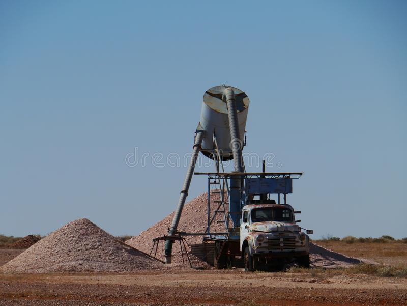 Colorful earth hills with a truck. Coober Pedy is a town in northern South Australia at the Stuart Highway and is famous for its opal mines stock image