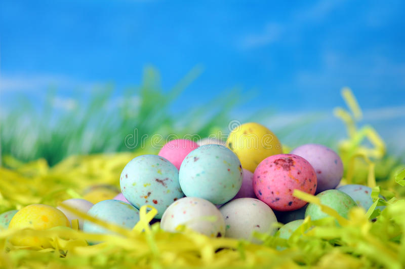 Colorful Easter candy on colorful paper nest royalty free stock photography