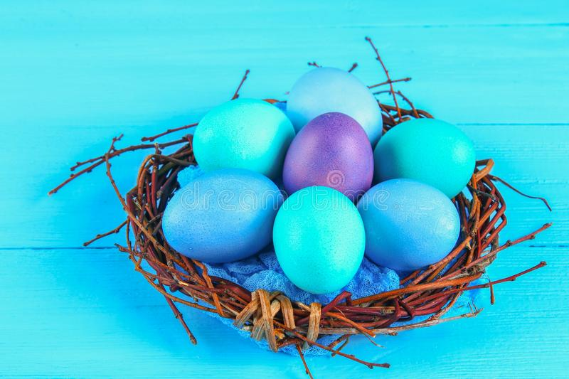 Colorful easter egg on blue pastel color wood background with space royalty free stock images