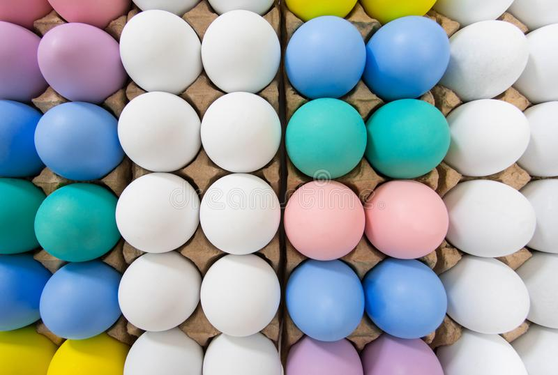 Colorful Easter egg in egg crate background pattern, flat lay view on a wide angle royalty free stock photography