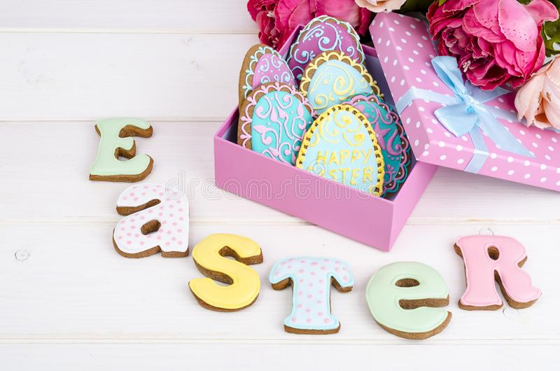 Colorful easter egg in gift box, cookies biscuits letter Easter on wood background. royalty free stock photos