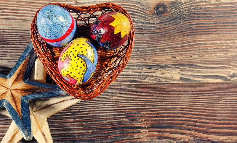 Colorful Easter Egg in a Heart Basket and Dry Starfish. Photo stock photo