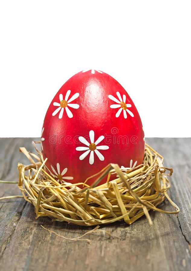 Colorful easter egg in the nest. On wooden table stock image
