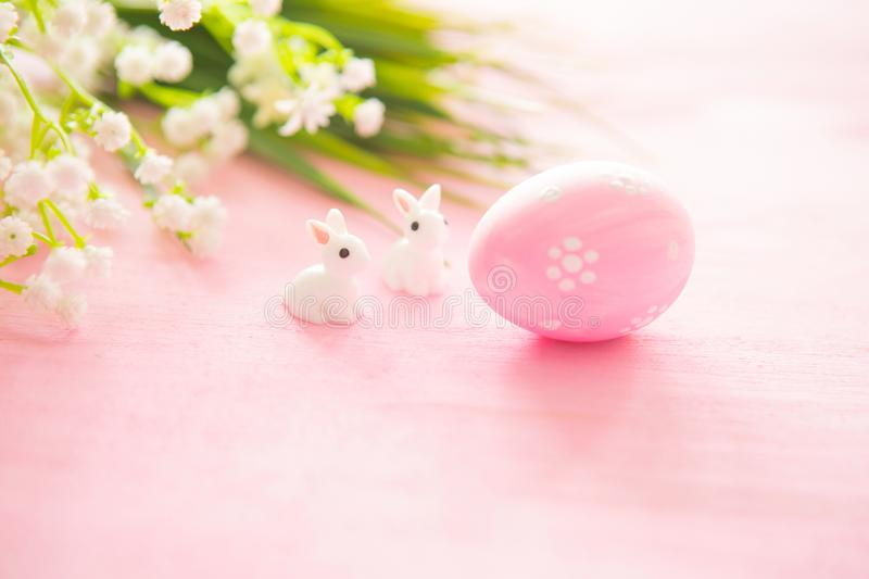 Colorful Easter egg with rabbits toy against a pink wood background.  royalty free stock image