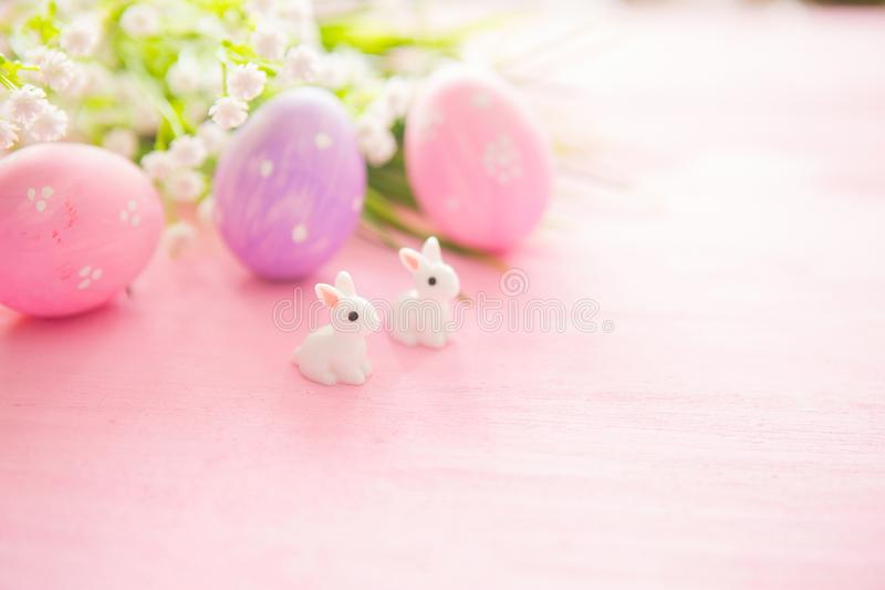 Colorful Easter egg with rabbits toy against a pink wood background.  stock photo