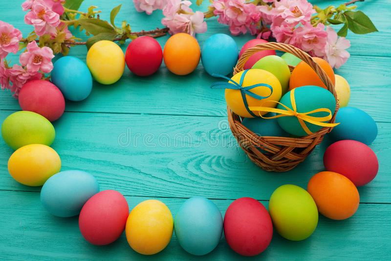 Colorful Easter Eggs and basket on blue wooden table background. Top view and copy space. Food Egg, flowers. Fun holiday royalty free stock images