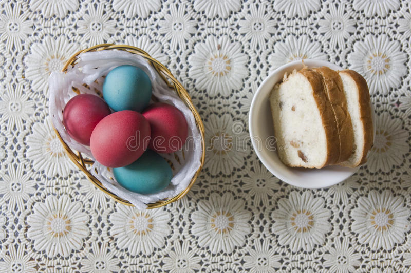 Colorful Easter eggs in a basket and bread stock photography