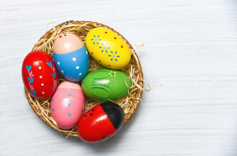 Colorful easter eggs basket nest decoration on white wooden background top view stock photography