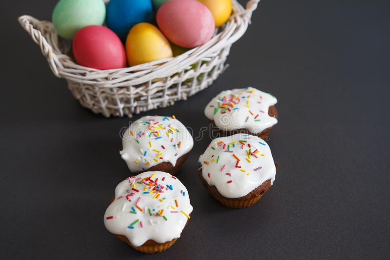 Colorful Easter eggs in basket and sweet muffins cupcakes on a black background. Easter background stock photo