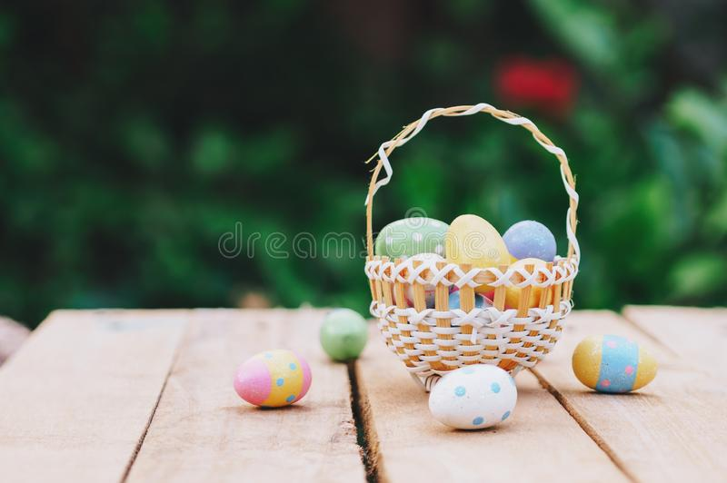 Colorful easter eggs in basket on wooden table win copy space.  royalty free stock photography