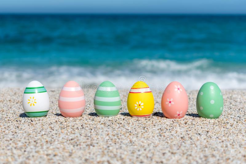 Colorful Easter eggs on the beach in sunny day. Easter concept stock photo