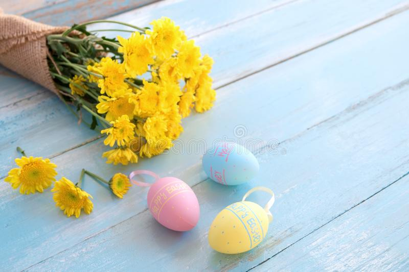 Colorful Easter eggs with bouquet of yellow chrysanthemum on blue wooden background. stock photo