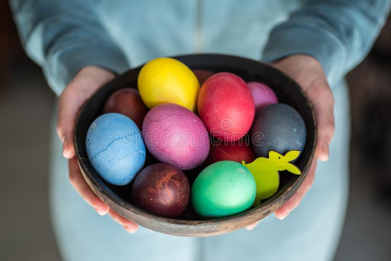 Colorful Easter eggs in bowl in woman`s hands.  stock images