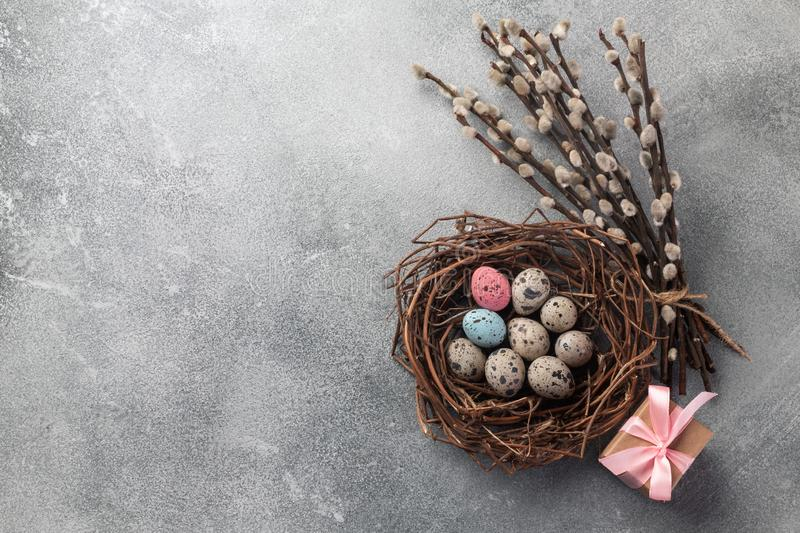 Colorful easter eggs in box and flowers on table. Top view with copy space.  royalty free stock image