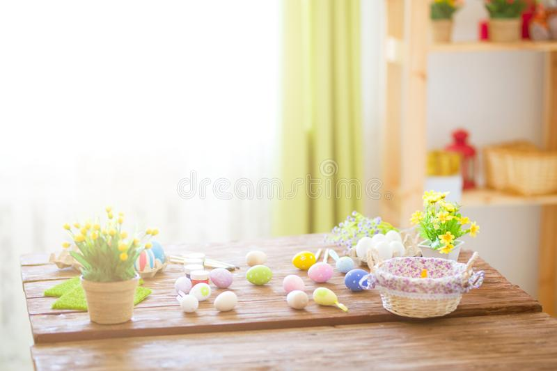 Colorful easter eggs and brushes on wooden table in home royalty free stock images