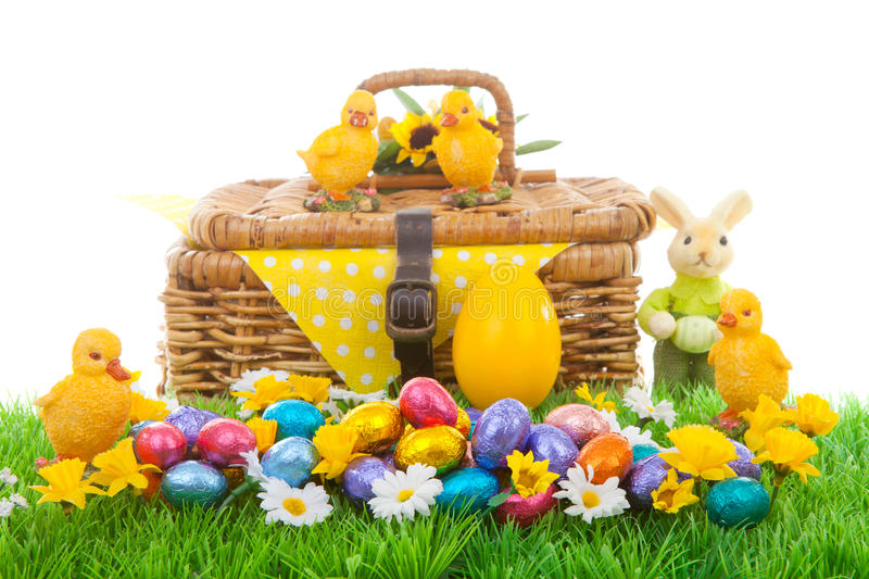 Easter arrangement. Colorful easter eggs, bunny, chickens and basket on green grass with flowers royalty free stock image