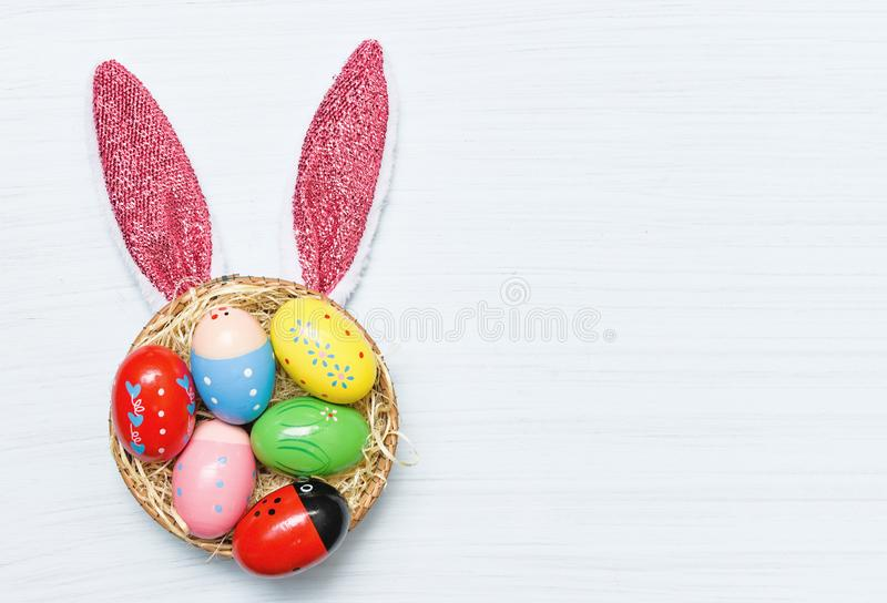 Colorful easter eggs and easter bunny ear rabbit in basket nest. Decoration on white wooden background top view royalty free stock photography