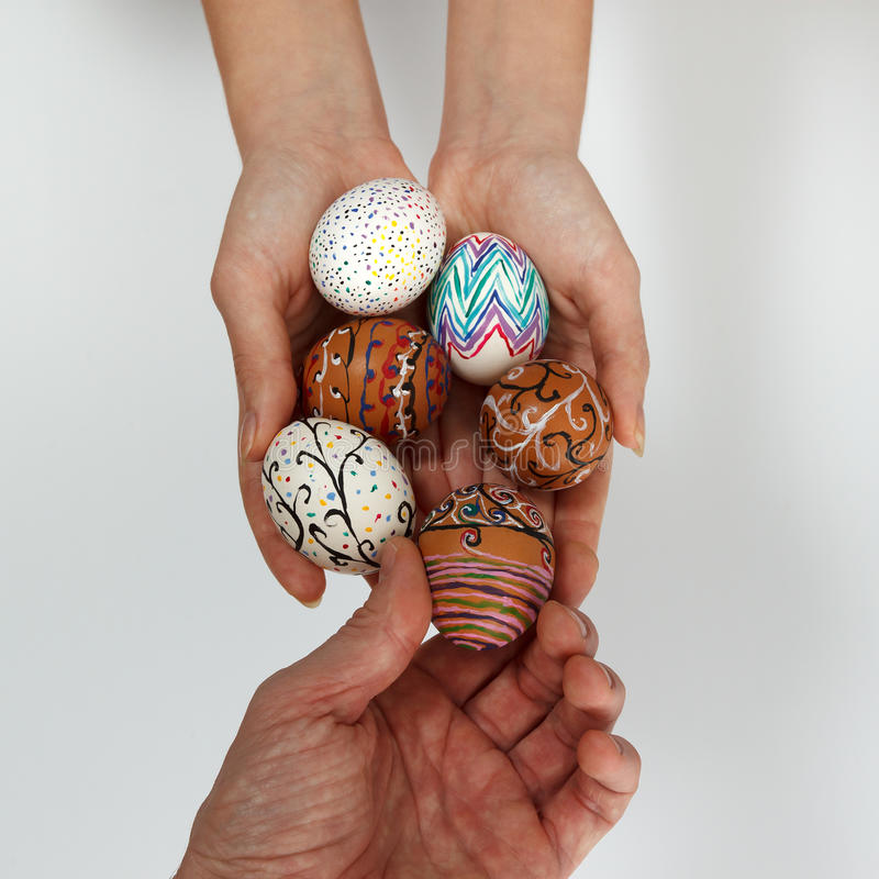 Colorful Easter eggs on burlap, female hand chose and pick one egg. Colorful Easter eggs in female hands, male hand chose and pick one egg against white royalty free stock photo