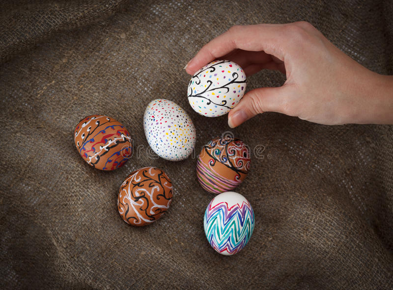 Colorful Easter eggs on burlap, female hand chose and pick one. Horizontal top view close up stock photos