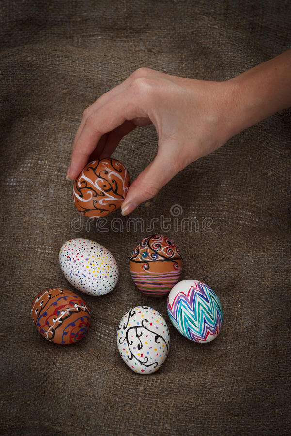 Colorful Easter eggs on burlap, female hand chose and pick one. Top view close up royalty free stock photos