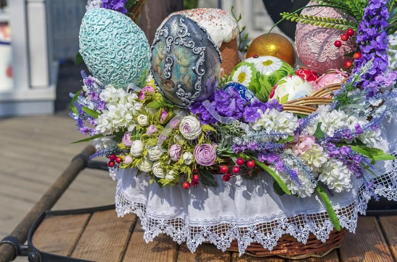 Colorful Easter eggs and Easter cakes in a wicker basket stock photography