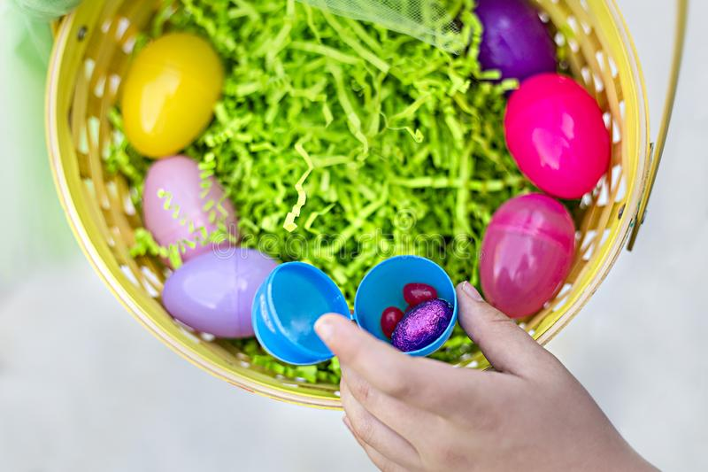 Colorful Easter eggs and candy in an Easter Basket. Holiday traditions. Close up view of an open plastic egg with Easter candy in it. A hand is pulling out candy royalty free stock image