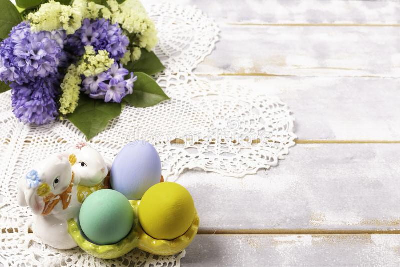 Colorful Easter eggs in a ceramic rabbit stand and a spring bouquet with lilac and yellow flowers on a beautiful knitted napkin on royalty free stock image